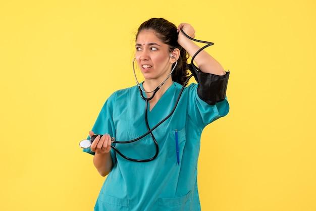 Widok z przodu zastanawiał się kobietę lekarza w mundurze trzymającą ciśnieniomierze, stojącą na żółtym tle