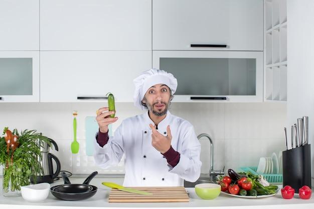 Widok z przodu zastanawiał się męski szef kuchni w mundurze trzymający ogórek w kuchni
