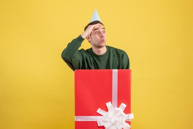Widok z przodu zastanawiał się młody człowiek w czapce imprezowej, stojący za dużym pudełkiem na prezent na żółto