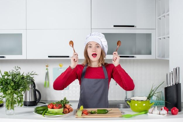 Widok z przodu zastanawiała się kobieta szefa kuchni w fartuchu trzymająca łyżki