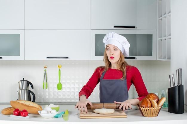 Widok z przodu zastanawiała się kobieta w kucharskiej czapce i fartuchu tocząca ciasto w kuchni