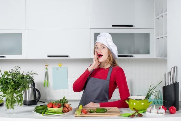 Widok z przodu zastanawiała się kucharka w fartuchu stojąca za stołem kuchennym
