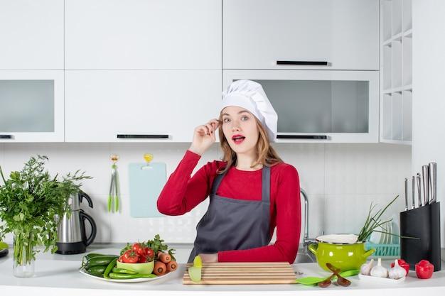 Widok z przodu zastanawiała się młoda kobieta w fartuchu stojąca w kuchni