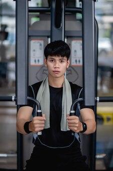 Widok z przodu, zbliżenie portret młody przystojny mężczyzna w odzieży sportowej siedzi do robienia ćwiczeń prasy klatki piersiowej maszyny w nowoczesnej siłowni, nie mogę się doczekać