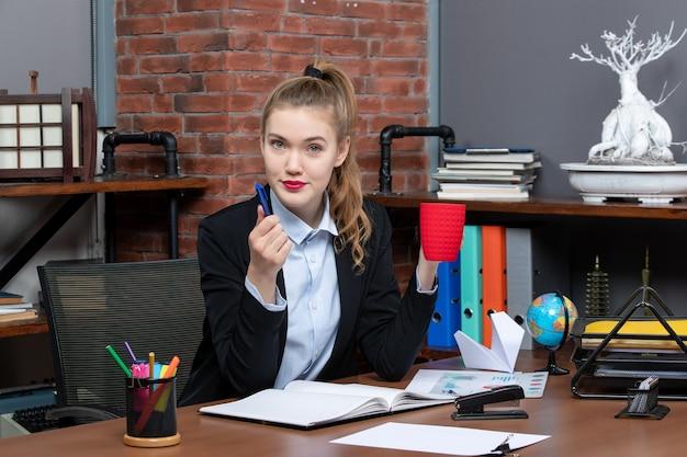 Widok z przodu zdeterminowanej młodej kobiety siedzącej przy stole i trzymającej czerwony kubek niebieski długopis w biurze