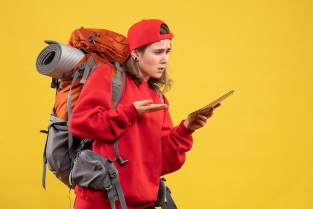 Widok z przodu zdezorientowana kobieta z plecakiem w czerwonym swetrze trzymająca mapę podróży