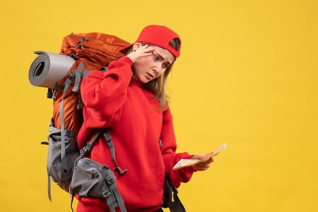 Widok z przodu zdezorientowana turystka z plecakiem trzymającym mapę podróży