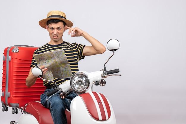 Widok z przodu zdezorientowanego młodego człowieka ze słomkowym kapeluszem na motorowerze wyszukiwania lokalizacji na mapie