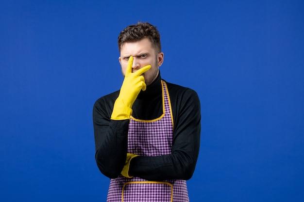 Widok z przodu zdezorientowanego młodego mężczyzny kładącego rękę na twarzy stojącego na niebieskiej ścianie