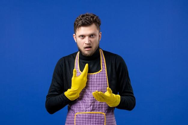 Widok z przodu zdezorientowanego młodego mężczyzny wskazującego na siebie stojącego na niebieskiej ścianie