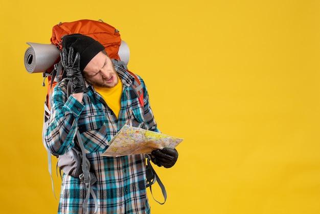 Widok z przodu zdezorientowanego młodego turysty ze skórzanymi rękawiczkami i plecakiem z mapą