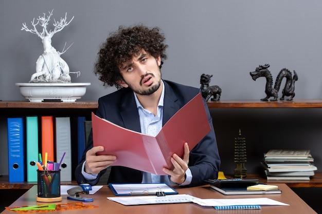 Widok z przodu zdezorientowany biznesmen siedzący przy biurku z papierami w swoim biurze