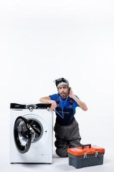 Widok z przodu zdezorientowany mechanik siedzący w pobliżu pralki, słuchający czegoś na białej przestrzeni