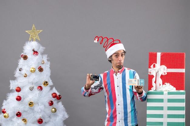 Widok z przodu zdezorientowany mężczyzna trzyma kartę i bilet podróżny wokół choinki i prezentów