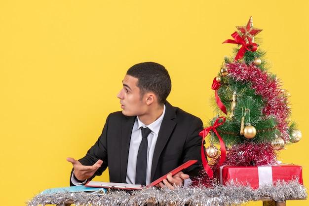 Widok z przodu zdezorientowany mężczyzna w garniturze siedzi przy stole trzymając dokument patrząc na prawo na boże narodzenie drzewo i prezenty