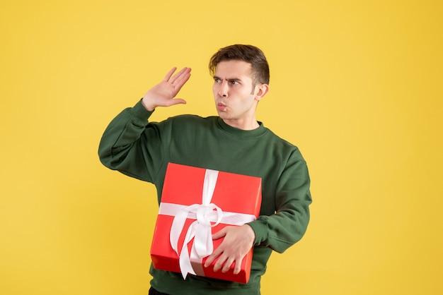 Widok z przodu zdezorientowany mężczyzna w zielonym swetrze wita kogoś na żółto