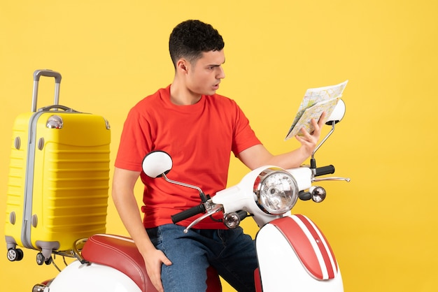 Widok z przodu zdezorientowany młody człowiek na motorowerze patrząc na mapę