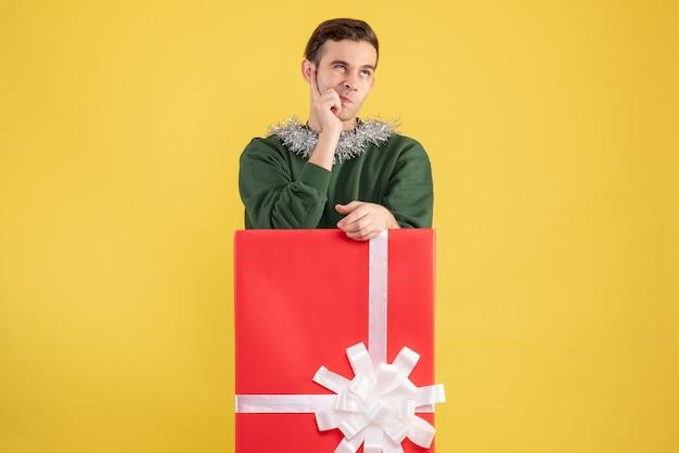 Widok z przodu zdezorientowany młody człowiek stojący za dużym pudełkiem na prezent na żółto