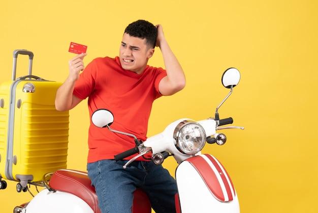 Widok z przodu zdezorientowany młody człowiek w czerwonej koszulce na motorowerze trzyma kartę
