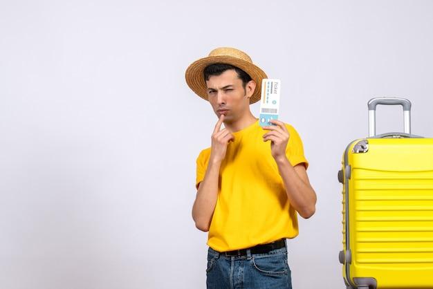 Widok z przodu zdezorientowany młody turysta w żółtej koszulce stojącej w pobliżu walizki trzymającej bilet lotniczy