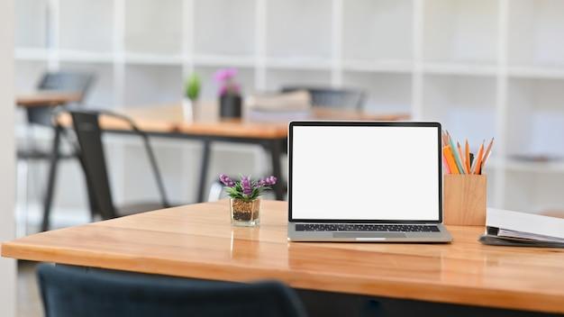 Widok z przodu zdjęcie białego pustego ekranu laptopa na biurku. w tym uchwyt na ołówek, teczki na dokumenty i roślina doniczkowa na biurku.