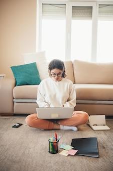 Widok z przodu zdjęcie kaukaskiej kobiety w okularach odrabiania lekcji na podłodze za pomocą laptopa i folderów