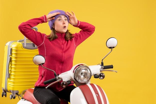 Widok z przodu zdumiał młodą dziewczynę na motorowerze, patrząc na coś z wielkim zainteresowaniem