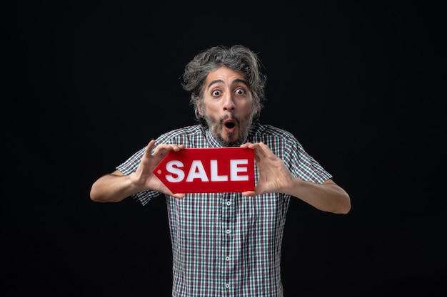 Widok z przodu zdumiony mężczyzna trzymający znak sprzedaży obiema rękami stojący na ciemnej ścianie