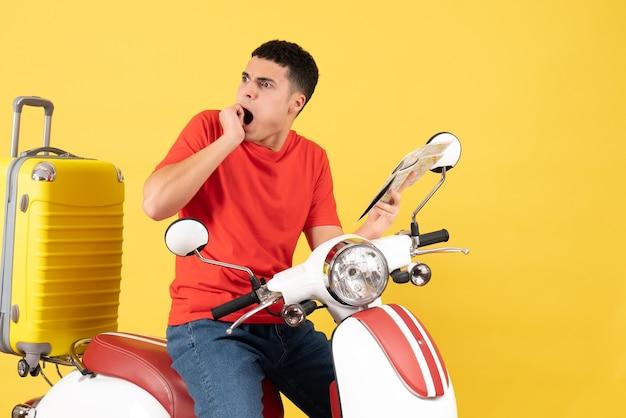 Widok z przodu zdumiony młody człowiek na mapie gospodarstwa motoroweru