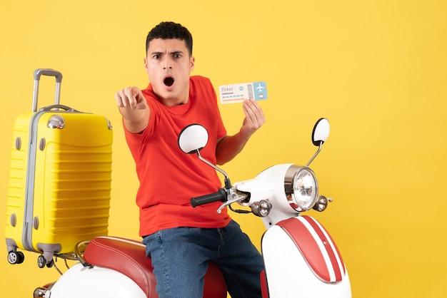 Widok z przodu zdumiony młody mężczyzna w ubranie na motorowerze trzymając bilet, wskazując na coś