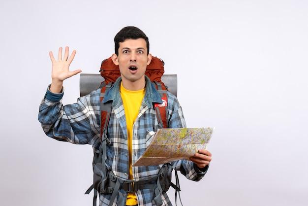 Widok z przodu zdumiony młody obozowicz z plecakiem trzymającym mapę machającą ręką