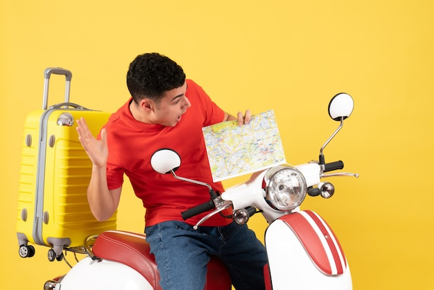 Widok z przodu zdumiony przystojny mężczyzna na mapie gospodarstwa motoroweru
