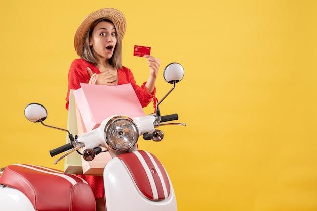 Widok z przodu zdumiony szczęśliwą kobietą w czerwonej sukience na motorowerze, trzymając torby na zakupy i karty