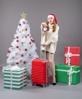 Widok z przodu zdziwiona blondynka w kapeluszu mikołaja trzyma czerwony budzik w pobliżu białego choinki i prezentów