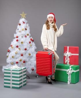 Widok z przodu zdziwiona świąteczna dziewczyna w czapce mikołaja, trzymająca torbę podróżną w pobliżu choinki i pudełek z prezentami