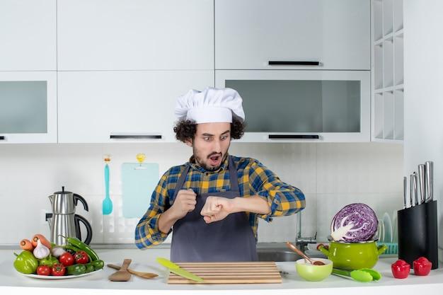 Widok z przodu zdziwionego męskiego szefa kuchni ze świeżymi warzywami i gotowaniem za pomocą narzędzi kuchennych i sprawdzaniem czasu w białej kuchni
