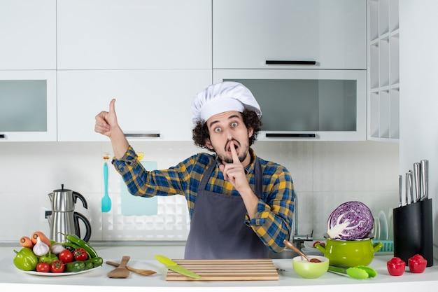 Widok z przodu zdziwionego męskiego szefa kuchni ze świeżymi warzywami i gotowaniem za pomocą narzędzi kuchennych oraz robieniem ciszy i ok gestu w białej kuchni