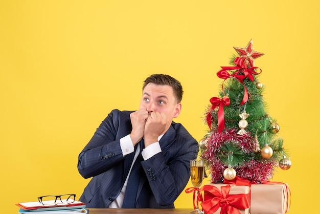 Widok z przodu zdziwionego mężczyzny patrząc na coś siedzącego przy stole w pobliżu choinki i prezentów na żółto