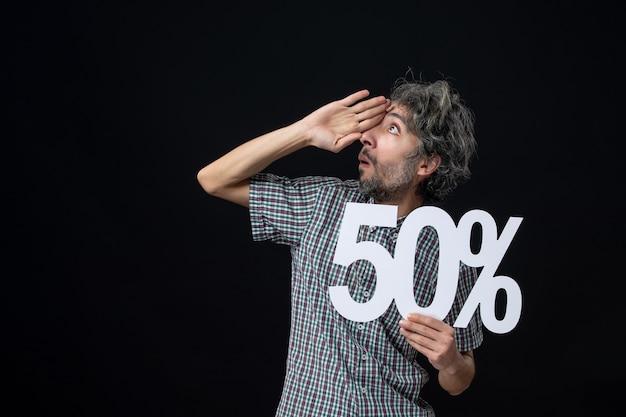 Widok z przodu zdziwionego mężczyzny trzymającego znak na ciemnej izolowanej ścianie