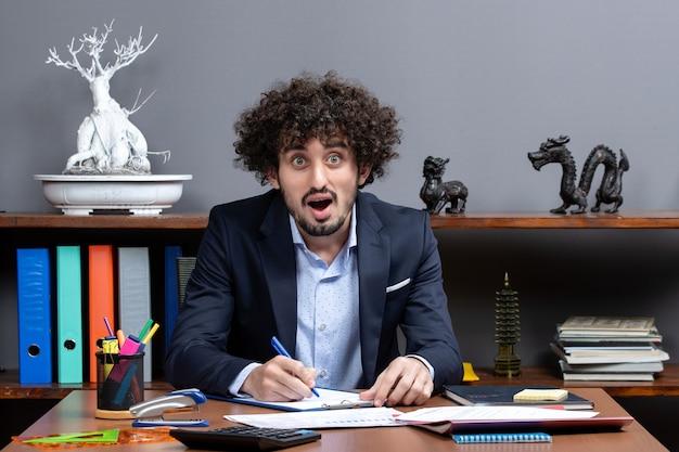 Widok z przodu zdziwionego młodego biznesmena siedzącego przy biurku, piszącego coś