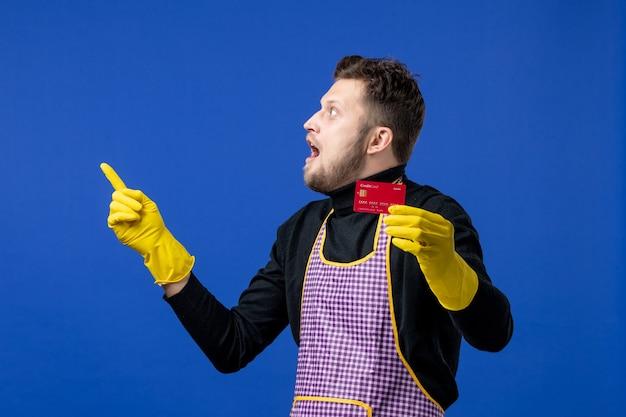 Widok z przodu zdziwionego młodego mężczyzny wskazującego na lewą kartę trzymającą na niebieskiej ścianie