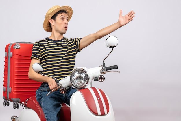 Widok z przodu zdziwionego młodzieńca w słomkowym kapeluszu na motorowerze sięgającym ręką