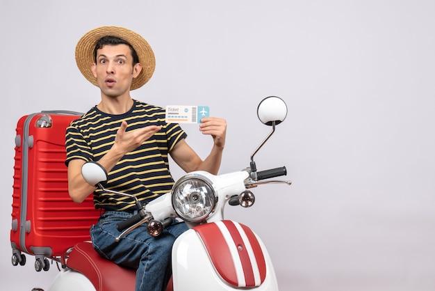 Widok z przodu zdziwionego młodzieńca w słomkowym kapeluszu na motorowerze, wskazując na bilet lotniczy