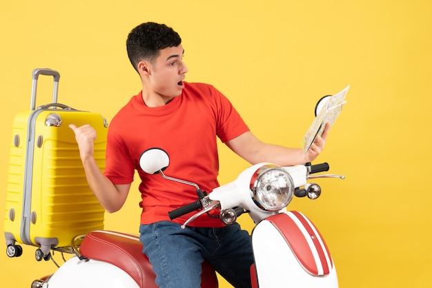 Widok z przodu zdziwiony młody człowiek na motorowerze patrząc na mapę