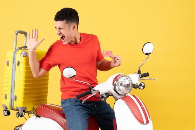 Widok z przodu zdziwiony młody człowiek na motorowerze trzymając kartę kredytową