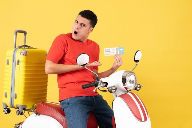 Widok z przodu zdziwiony młody mężczyzna w zwykłych ubraniach na bilet na motorower