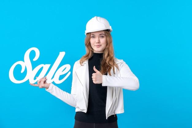 Widok z przodu żeński architekt trzymający sprzedaż piszący na niebiesko