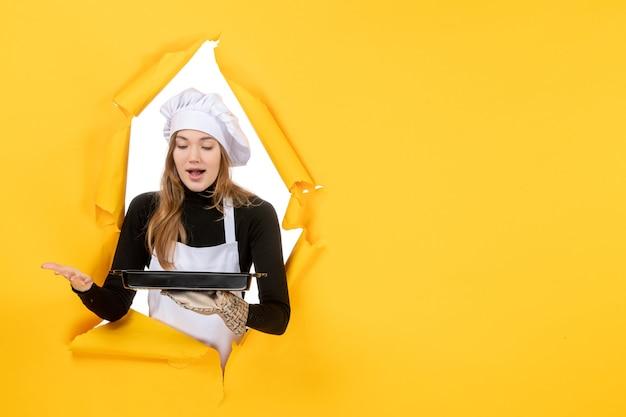 Widok z przodu żeński cukiernik trzymający czarną patelnię z ciastkami na żółtym zdjęciu emocje słońce jedzenie kuchnia kuchnia kolor praca