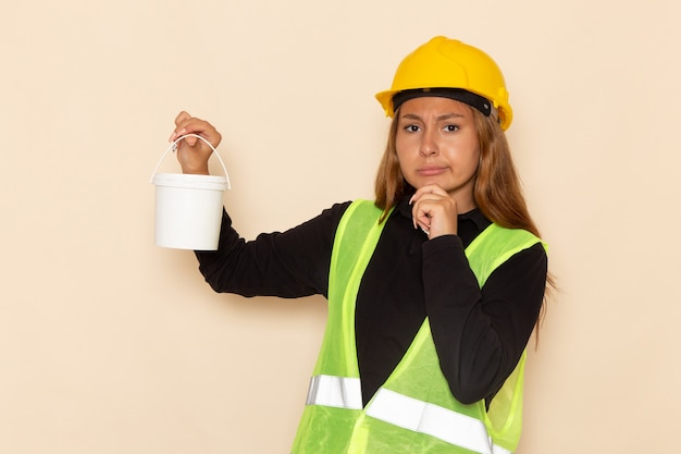 Widok z przodu żeński konstruktor w żółtej koszuli czarny kask trzyma farbę i myślenia na białym biurku kobieta architekta konstruktora