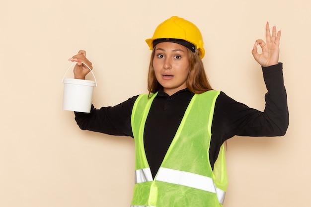 Widok z przodu żeński konstruktor w żółtej koszuli kasku trzyma farbę z w porządku znak na białej ścianie kobieta architekta konstruktora